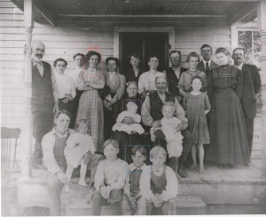 Nettie and extended family, farm porch (circa 1910). Helen (baby on lap of grandmother); Dwight, Nettie's son from her first marriage, the boy in the middle, front row.